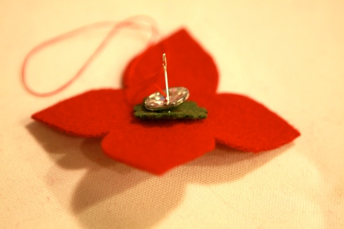 Cut out a green felt circle that is sewn to the small flower behind to accent the button.