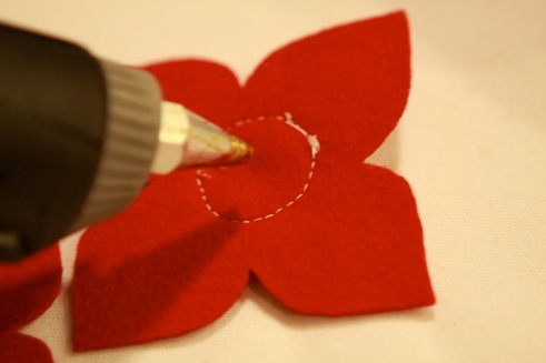 Hot glue the flower with the button on top of the large flower.